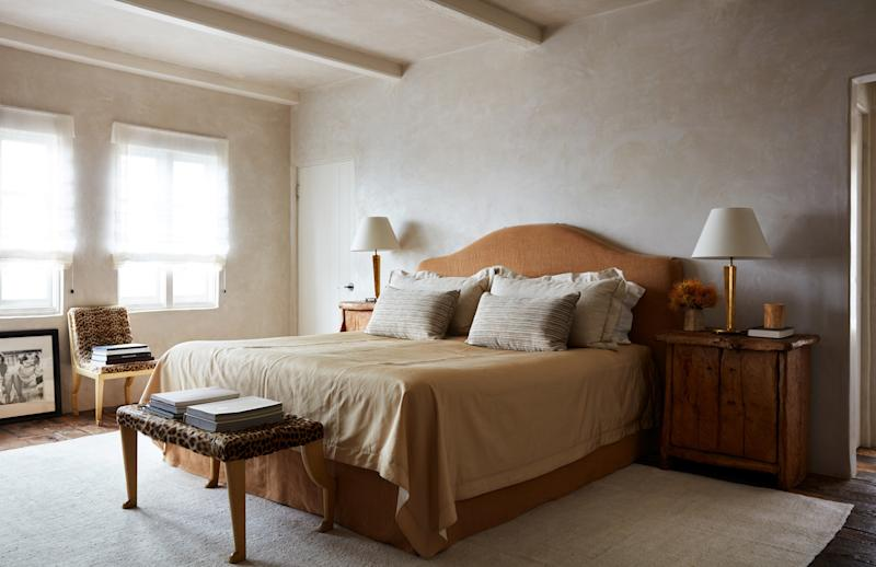 The master bedroom features a Hästens bed with Frette linens and a headboard covered in a linen by Anne Kirk Textiles. Vintage chair, stool, and table lamps by Marc Du Plantier.