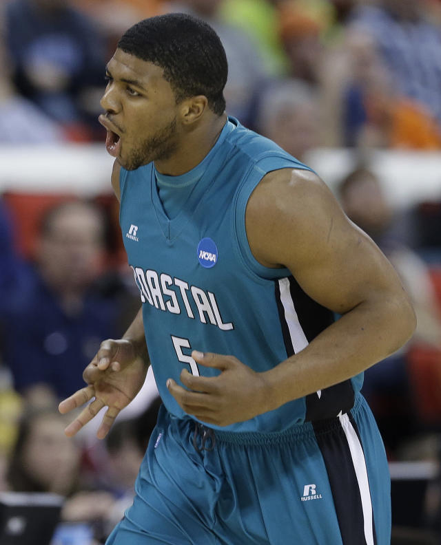 Coastal Carolina guard Eric Smith (5) celebrates a three-point shot against Virginia during the first half of an NCAA college basketball second-round tournament game, Friday, March 21, 2014, in Raleigh. (AP Photo/Gerry Broome)