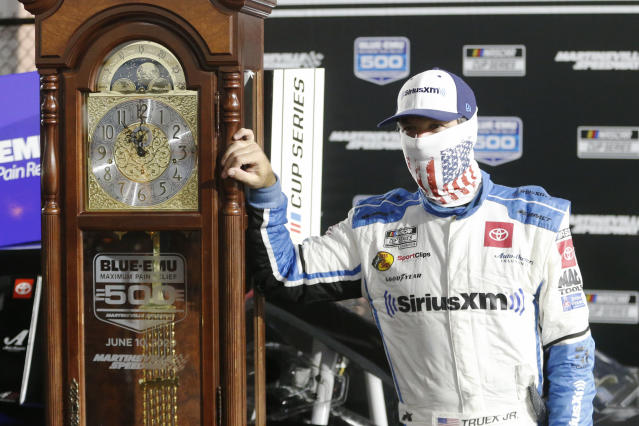 Martin Truex Jr. poses with his grandfather clock trophy after winning a NASCAR Cup Series auto race Wednesday, June 10, 2020, in Martinsville, Va. (AP Photo/Steve Helber)