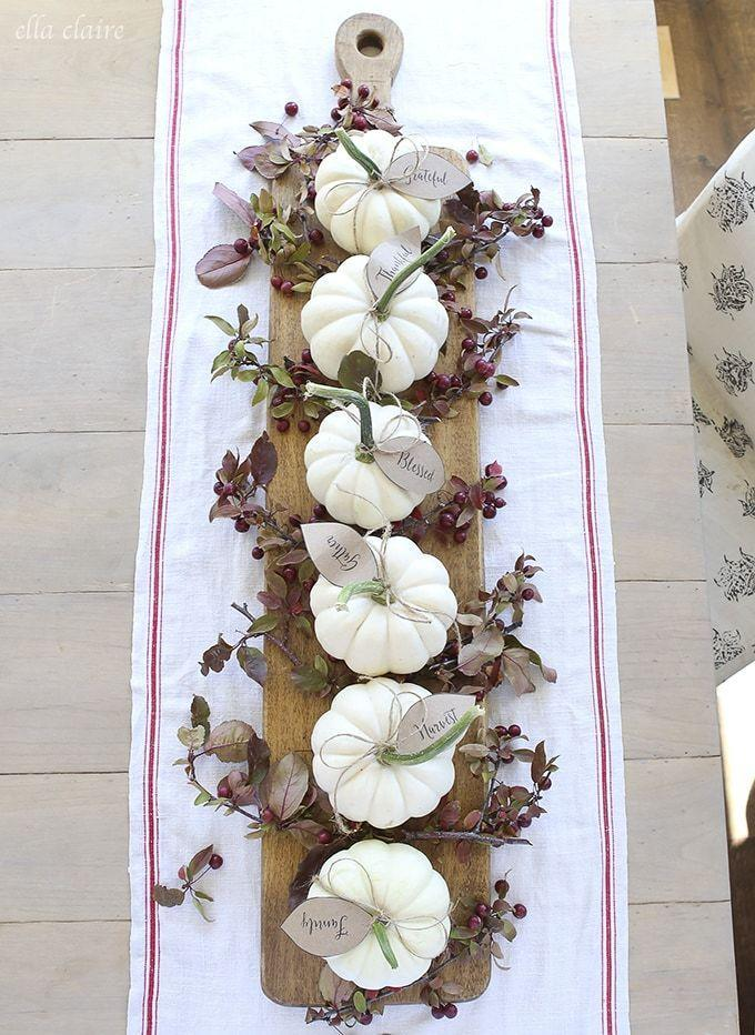 """<p>Those little leaf tags contain different words related to Thanksgiving, and they're offered as a free printable. Just add miniature white pumpkins, and you've got yourself an incredibly memorable centerpiece.</p><p><strong>Get the tutorial at <a href=""""https://www.ellaclaireinspired.com/pumpkin-leaves-free-printable/"""" rel=""""nofollow noopener"""" target=""""_blank"""" data-ylk=""""slk:Ella Claire Inspired"""" class=""""link rapid-noclick-resp"""">Ella Claire Inspired</a>.</strong></p><p><strong><strong><strong><a class=""""link rapid-noclick-resp"""" href=""""https://go.redirectingat.com?id=74968X1596630&url=https%3A%2F%2Fwww.walmart.com%2Fsearch%2F%3Fquery%3Dfaux%2Bpumpkins&sref=https%3A%2F%2Fwww.thepioneerwoman.com%2Fhome-lifestyle%2Fdecorating-ideas%2Fg36664123%2Fwhite-pumpkin-decor-ideas%2F"""" rel=""""nofollow noopener"""" target=""""_blank"""" data-ylk=""""slk:SHOP FAUX PUMPKINS"""">SHOP FAUX PUMPKINS</a></strong></strong><br></strong></p>"""