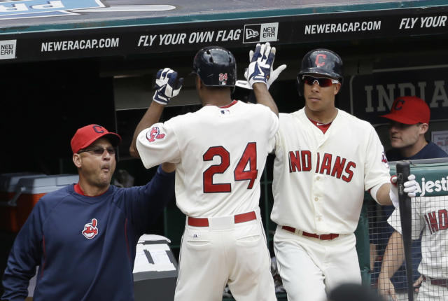 Cleveland Indians' Michael Bourn, center, is congratulated by manager Terry Francona, left, and Michael Brantley in the fifth inning of a baseball game against the Texas Rangers, Sunday, July 28, 2013, in Cleveland. Bourn scored on a single by Jason Kipnis. (AP Photo/Tony Dejak)