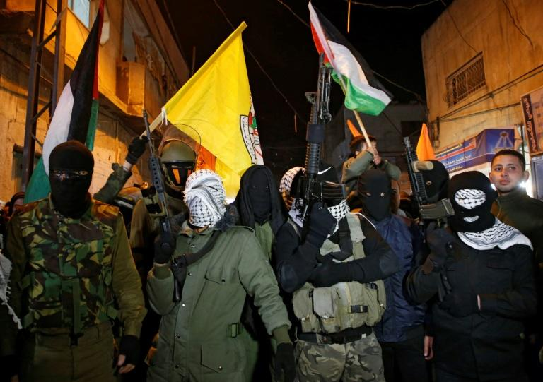 Palestinian militants of Al-Aqsa Martyrs Brigades demonstrate against the US president's recognition of Jerusalem as the capital of Israel at Al-Fawar refugee camp in the occupied West Bank