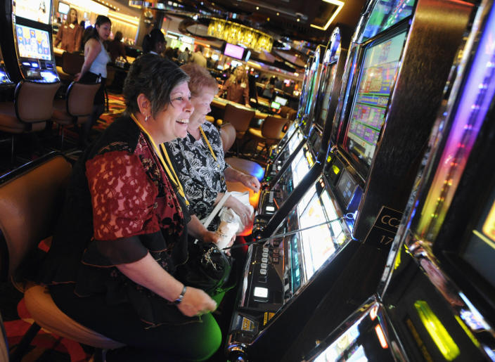 "FILE - In this July 15, 2011 file photo, Karen Lingermuth, of Niles, Ill., plays the slots during a special VIP event at the Rivers Casino in the Chicago suburb of Des Plaines, Ill. Chicago is taking a big step toward building its long-awaited first casino. Starting Thursday, April 22, 2021, city officials are officially seeking bids from companies interested in what's being billed as a ""world-class"" resort scheduled to open by 2025. (Mark Welsh/Daily Herald via AP, File)"