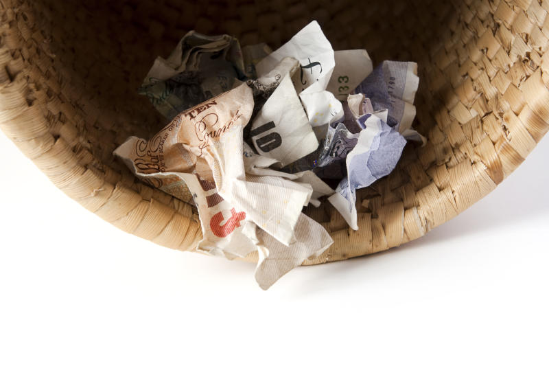 Crumpled banknotes in waste basket