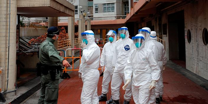 Police in protective gear wait to evacuate residents from a public housing building, following the outbreak of the novel coronavirus, in Hong Kong, China February 11, 2020. REUTERS/Tyrone Siu