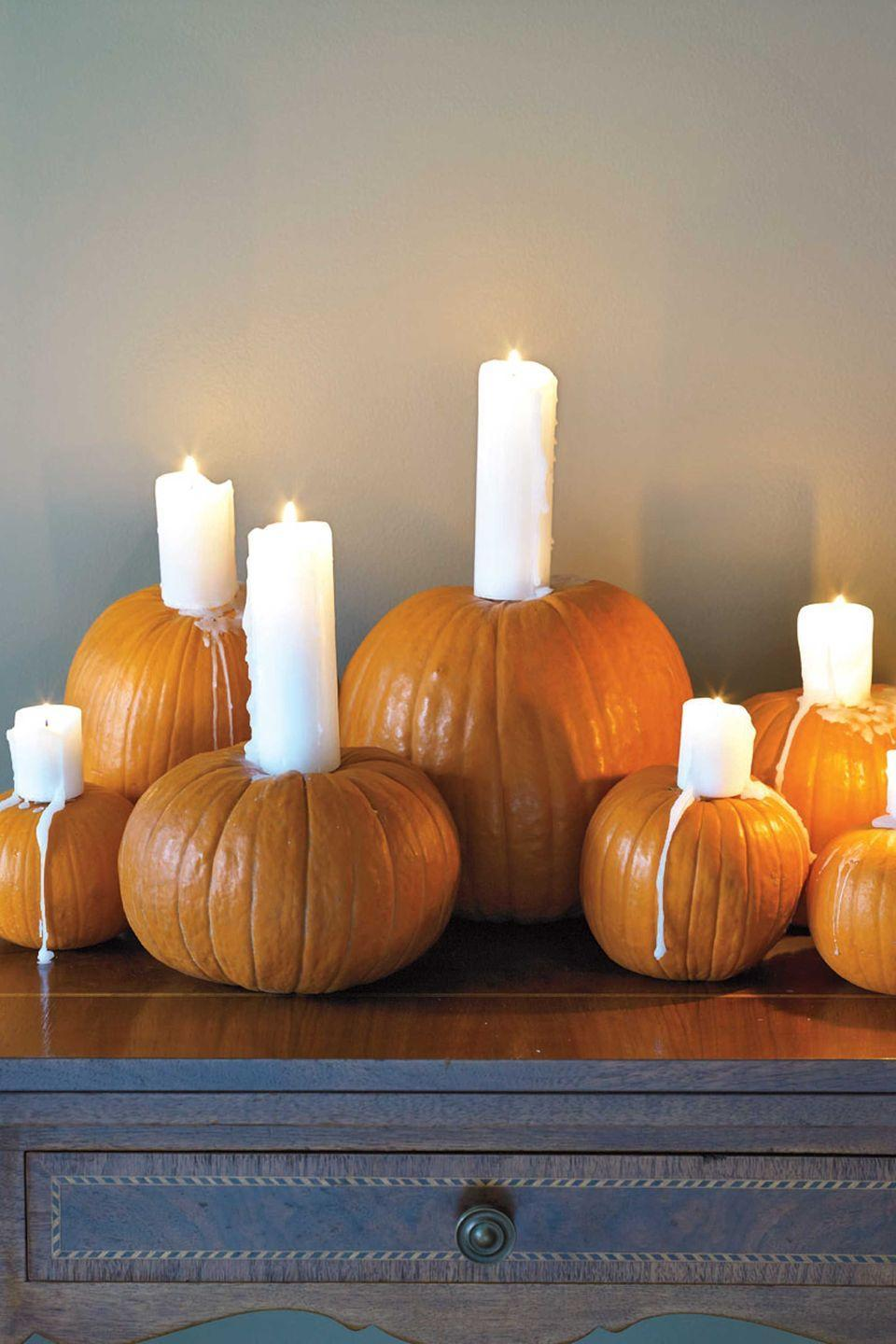"""<p>Feeling spooked? Brighten your space with these classy pumpkins outfitted with drip pillar candles.</p><p><strong><em><a href=""""https://www.womansday.com/home/crafts-projects/how-to/a5950/halloween-craft-how-to-candle-pumpkins-123346/"""" rel=""""nofollow noopener"""" target=""""_blank"""" data-ylk=""""slk:Get the Night Lights tutorial."""" class=""""link rapid-noclick-resp"""">Get the Night Lights tutorial.</a></em></strong></p>"""