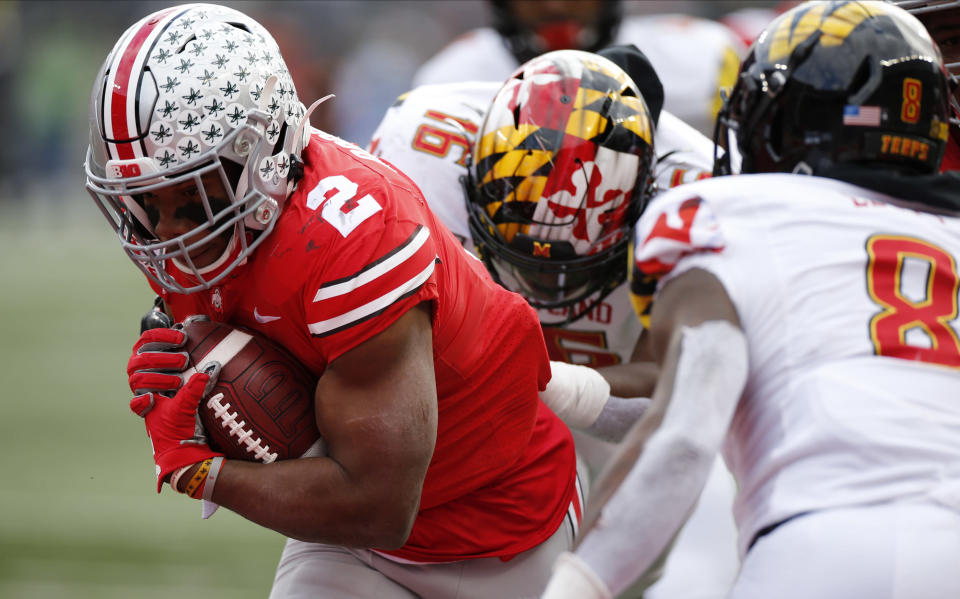 Ohio State running back J.K. Dobbins, left, breaks through the line of scrimmage to score a touchdown against Maryland during the first half of an NCAA college football game Saturday, Nov. 9, 2019, in Columbus, Ohio. (AP Photo/Jay LaPrete)