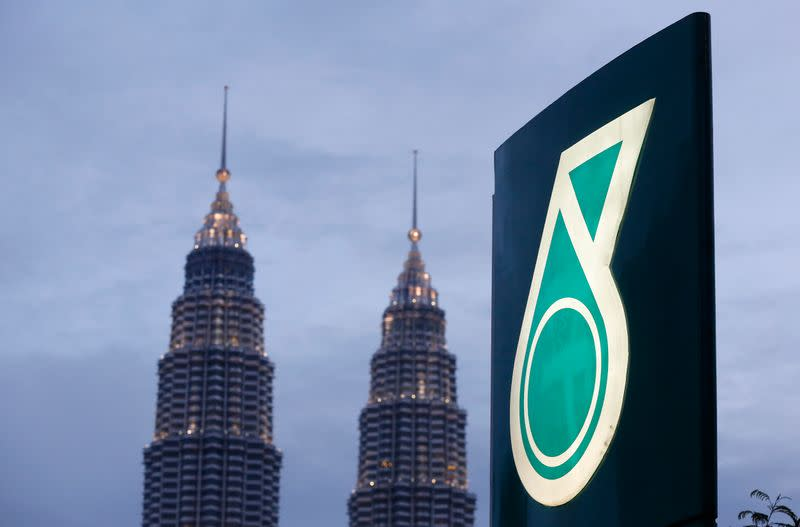 The logo of a Petronas fuel station is seen with the Petronas Twin Towers in the background in Kuala Lumpur