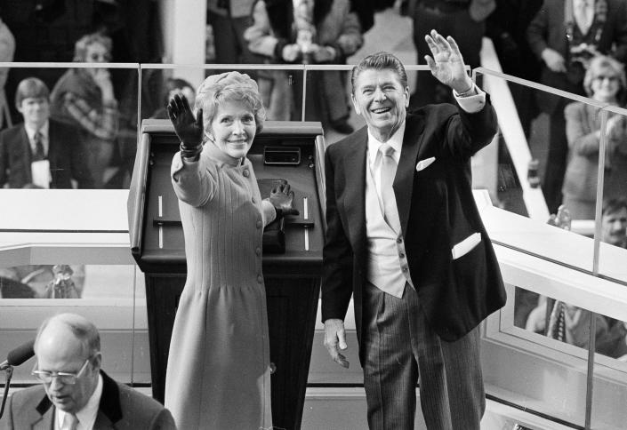 FILE - In this Jan. 20, 1981, file photo, President Ronald Reagan and first lady Nancy Reagan wave to onlookers at the Capitol building as they stand at the podium in Washington following the swearing in ceremony. (AP Photo/File)