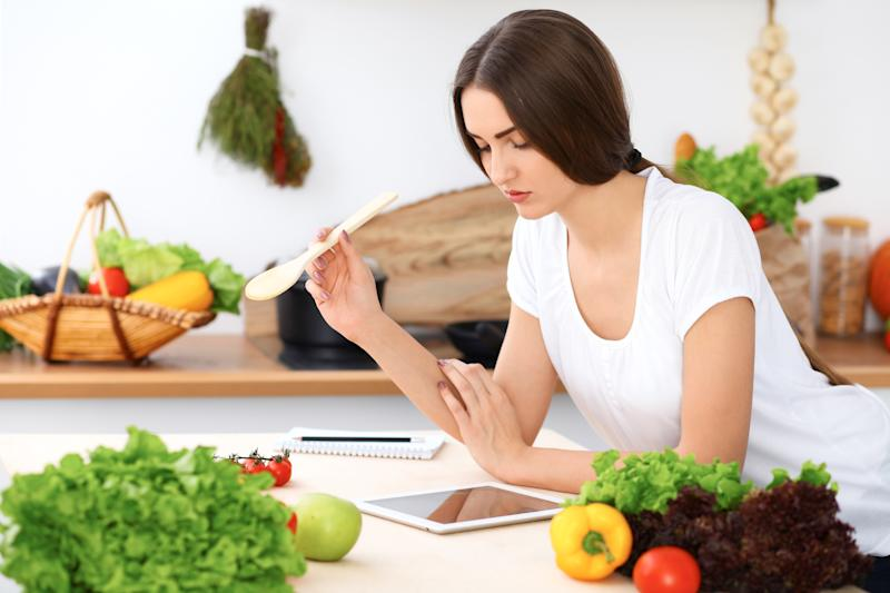 A young woman holding a wooden spoon while looking at a tablet on a kitchen counter with fresh produce.