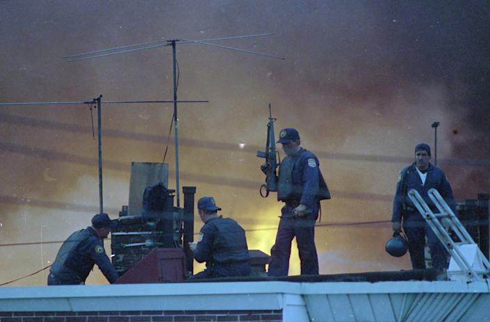 Armed Philadelphia police officers man a rooftop as the sky is illuminated by the flames from a neighborhood in West Philadelphia, Pennsylvania, that burned after police dropped a bomb on a building occupied by members of MOVE on May 13, 1985.