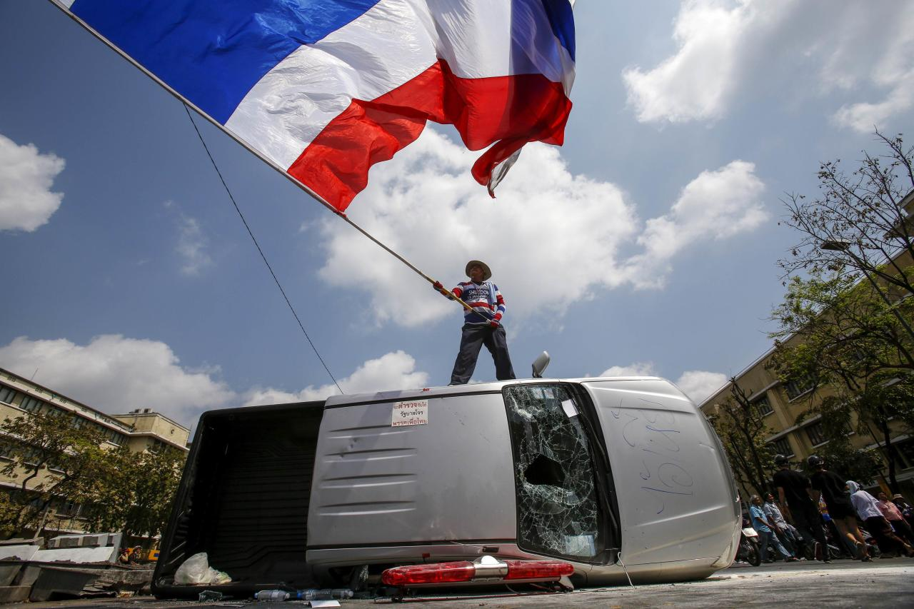 An anti-government protester stands on a damaged police vehicle as he waves a Thai national flag after clashes with riot police officers near the Government House in Bangkok February 18, 2014. A Thai police officer was killed and dozens of police and anti-government protesters were wounded in gun battles and clashes in Bangkok on Tuesday, officials and witnesses said. REUTERS/Athit Perawongmetha (THAILAND - Tags: POLITICS CIVIL UNREST TPX IMAGES OF THE DAY)