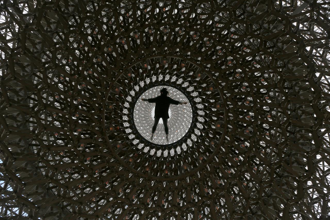 <p>A member of Kew staff poses with Wolfgang Buttress' sculpture The Hive at Kew Gardens in London, Britain June 15, 2016. (REUTERS/Neil Hall) </p>