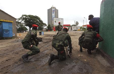 Congolese security officers position themselves as they secure the street near the state television headquarters (C) in the capital Kinshasa, December 30, 2013. REUTERS/Jean Robert N'Kengo