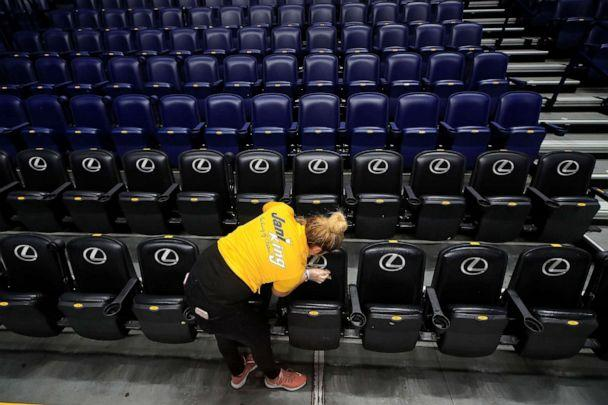 PHOTO: A worker cleans the seats after the announcement of the cancellation of the SEC Basketball Tournament due to the coronavirus at Bridgestone Arena, March 12, 2020, in Nashville, Tenn. (Andy Lyons/Getty Images)