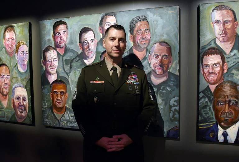 Command Sergeant Major Brian Flom, pictured next to a painting of himself by former president George W. Bush, was wounded in the face by a rocket attack in Iraq in 2007 (AFP Photo/Olivier Douliery)