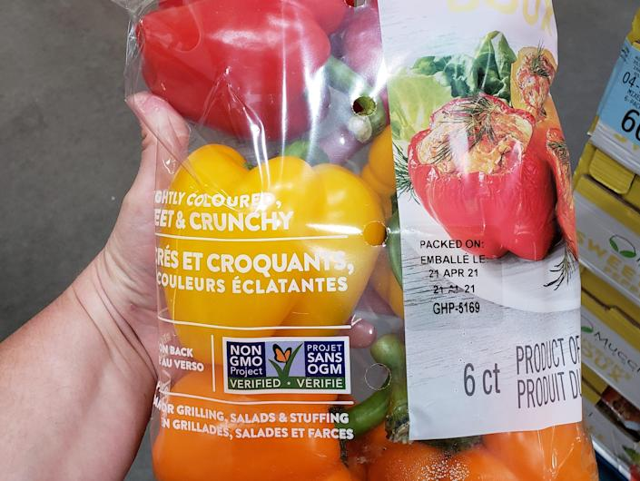 hand holding a bulk bag of tri-colored bell peppers at costco