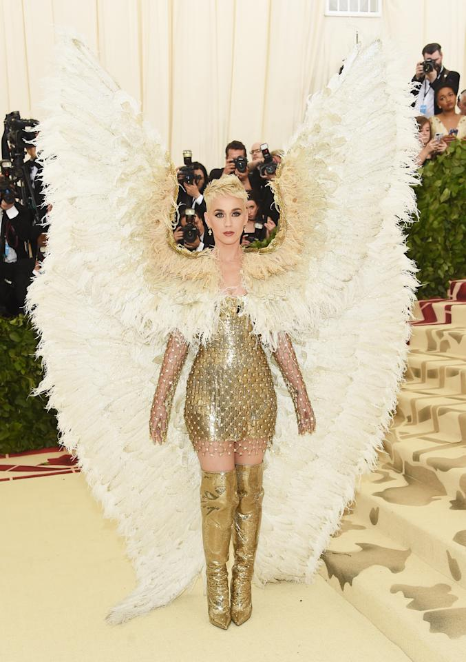 <p>The popstar dominated the red carpet in this gold Cersave minidress, thigh-high gold boots and a pair of massive angel wings. Photo: Getty Images </p>
