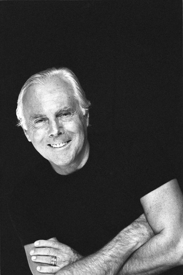 Italian fashion designer Giorgio Armani smiles as he poses with his arms crossed, early 1990s. (Photo by Andrea Blanch/Getty Images)
