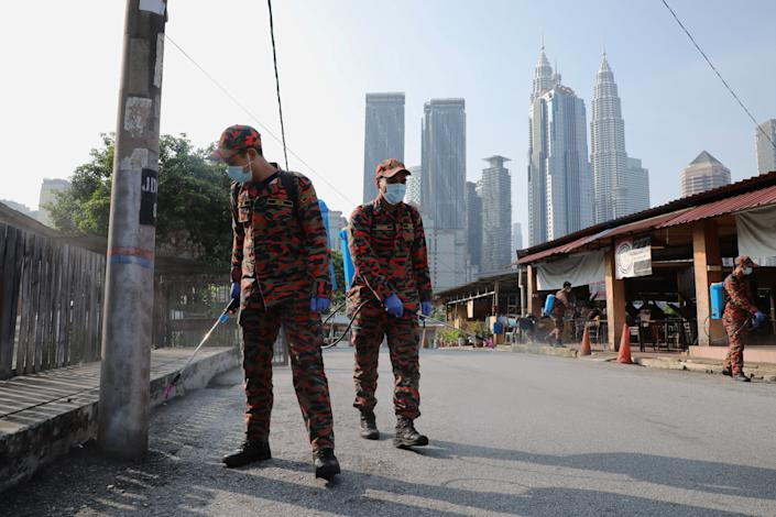 Firefighters spray disinfectant on a street during the lockdown in Kuala Lumpur, Malaysia. (Reuters)