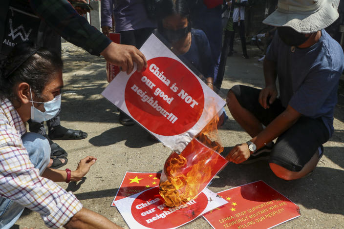Anti-coup protesters burn a representation of the Chinese national flag during a demonstration in Yangon, Myanmar on Wednesday, April 7, 2021. Threats of lethal violence and arrests of protesters have failed to suppress daily demonstrations across Myanmar demanding the military step down and reinstate the democratically elected government. (AP Photo)