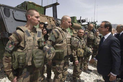 French President Francois Hollande reviews troops, on May 25, during a visit to a military base in Kapisa, in Afghanistan, where most French troops are stationed in Afghanistan. Hollande said on Friday that France would coordinate with NATO allies the withdrawal of its combat troops from Afghanistan