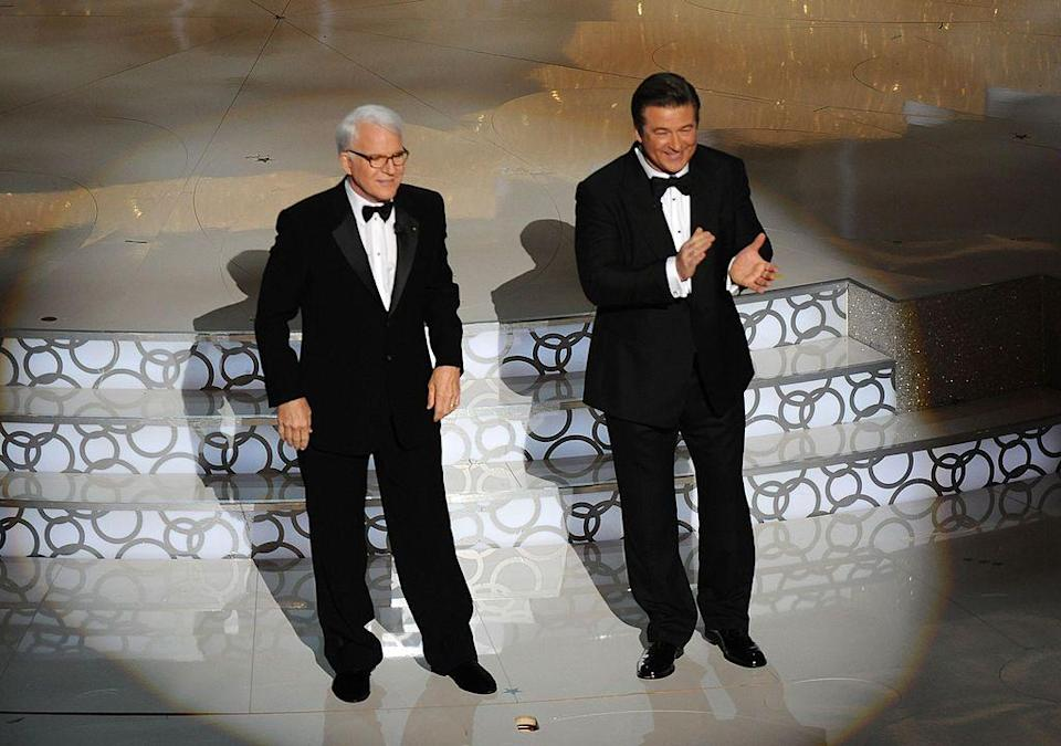 <p>The Father Of The Bride actor has hosted the actors solo twice before, but in 2010 returned with Alec Baldwin. </p><p>The actors arrived to deliver their monologue from the ceiling (with Cabaret feather dancers either side of them) where they gave some old-school Hollywood simple jokes: 'Oh there's that damn Helen Mirren...' 'Oh no, that's Dame Helen Mirren.'</p>