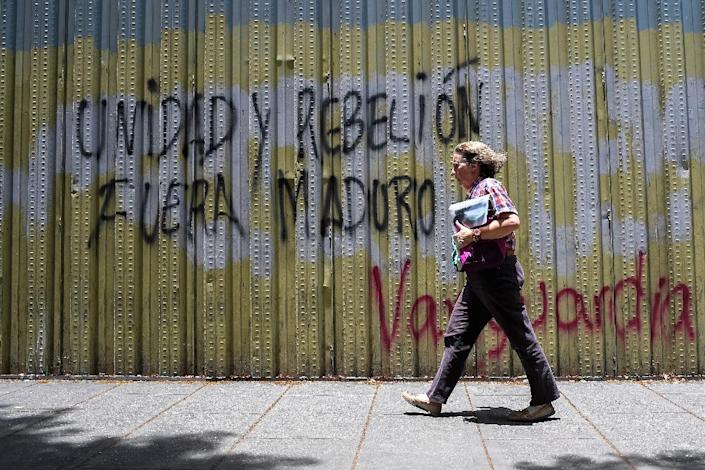 A woman walks past graffiti that reads 'Unity and rebellion, Maduro should go' in Caracas (AFP Photo/Federico PARRA)