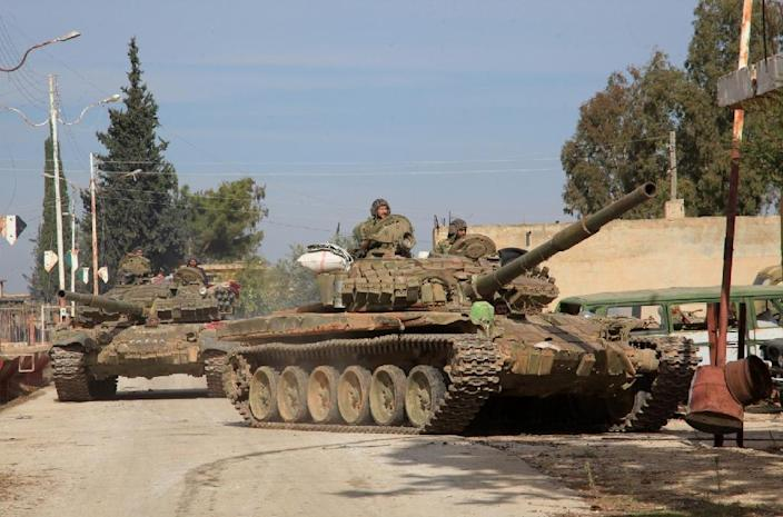 Syrian army tanks enter a village near the Kweyris military air base, in the east of the northern Syrian province of Aleppo, on November 15, 2015 (AFP Photo/George Ourfalian)