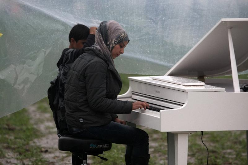 Syrian Nour Alkhzam, 24, plays the piano during a concert organized by Chinese artist Ai Weiwei at the Greek-Macedonian border near the Greek village of Idomeni, on March 12, 2016 (AFP Photo/Sakis Mitrolidis)