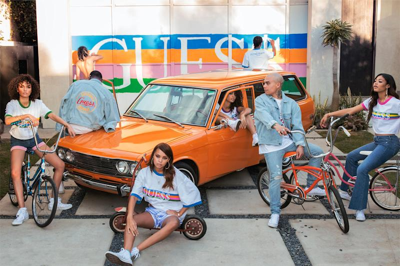 Several models wearing jeans and jean shorts in front of an old orange car in front of a Guess logo on the back wall.