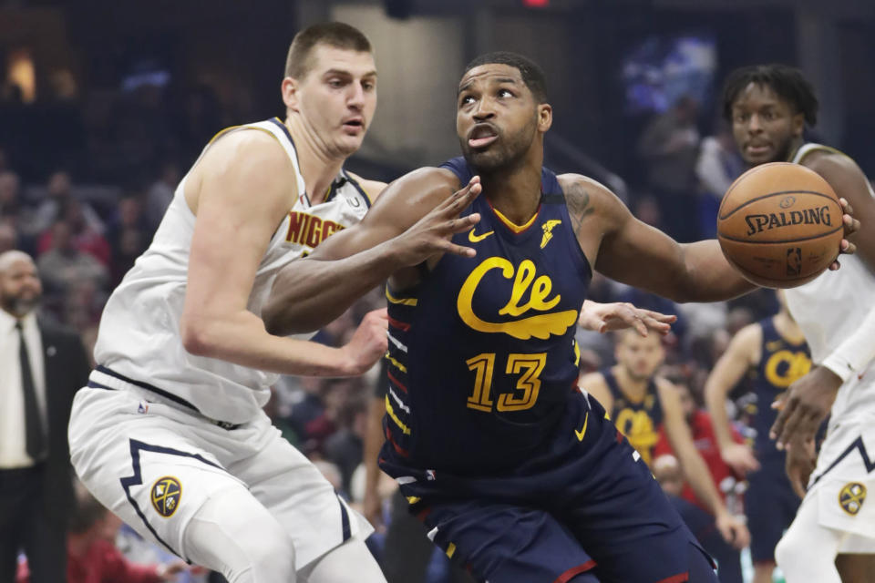 Cleveland Cavaliers' Tristan Thompson, right, drives past Denver Nuggets' Nikola Jokic in the first half of an NBA basketball game, Saturday, March 7, 2020, in Cleveland. (AP Photo/Tony Dejak)