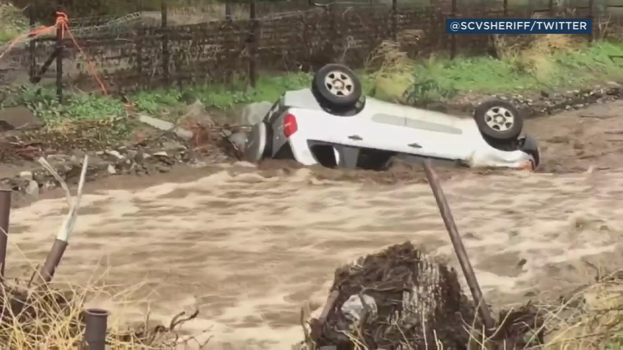 Rushing floodwaters swept away a car in Santa Clarita, flipping the vehicle upside down Thursday.
