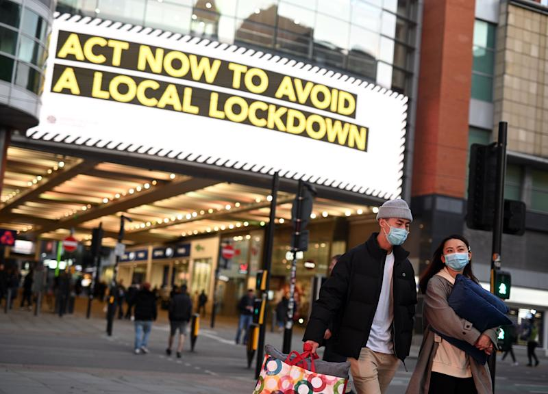 "People wearing face masks walk through the shopping area in the city centre of Manchester, north west England on October 8, 2020. - Pubs and restaurants in coronavirus hotspots look set to face fresh restrictions after Downing Street said new data suggests there is ""significant"" transmission taking place in hospitality settings. A ""range of measures"" is being looked at, with a particular focus on northern England, where it says infection rates are rising fastest. (Photo by Oli SCARFF / AFP) (Photo by OLI SCARFF/AFP via Getty Images)"