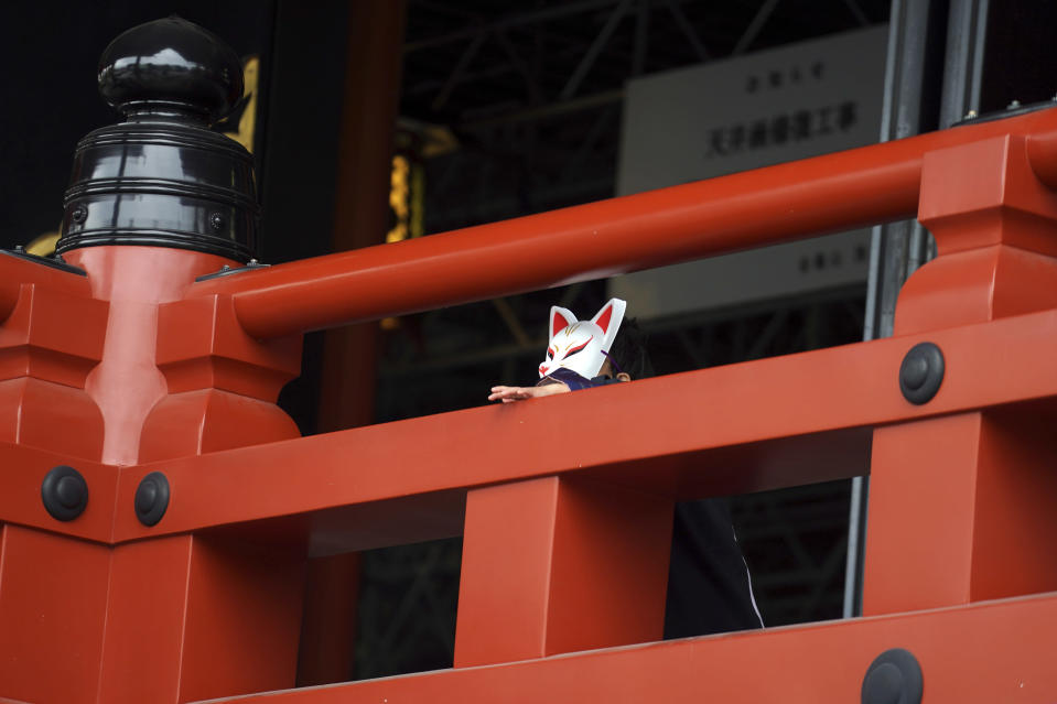 A child wearing traditional mask depicting fox pauses at a shrine Tuesday, Nov. 24, 2020, in Tokyo. The Japanese capital confirmed more than 180 new coronavirus cases on Tuesday. (AP Photo/Eugene Hoshiko)