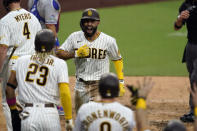San Diego Padres' Eric Hosmer, center, reacts with teammates after hitting a grand slam during the fifth inning of a baseball game against the Texas Rangers, Thursday, Aug. 20, 2020, in San Diego. (AP Photo/Gregory Bull)