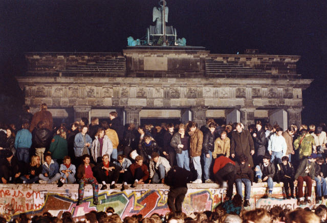 A crowd climbs the Berlin Wall in front of the Brandenburg Gate in West Berlin, Germany, as the Wall opened up at Checkpoint Charlie on Nov. 10, 1989. (Photo by John Tlumacki/The Boston Globe via Getty Images)