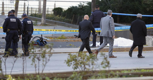 <p>New York Police Department officers investigate the scene around a body covered under a white sheet next to a mangled bike along the bike path, Oct. 31, 2017, in New York. (Photo: Bebeto Matthews/AP) </p>