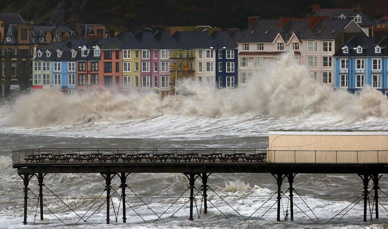 Waves crash against the promenade in Aberystwyth, Wales Monday Jan. 6, 2014 as strong winds and high tides continue in western Britain . Weather forecasting body the Met Office warned of wind gusts of up to 70 mph (113 kph), accompanied by exceptionally large waves, along the coasts of Wales, southwest England and Northern Ireland on Monday. The Environment Agency issued a severe flood warning meaning there is a threat to life and property — for the county of Dorset in southwestern England, as well as more than 300 less serious flood warnings and alerts. (AP Photo/Dave Thompson/PA) UNITED KINGDOM OUT