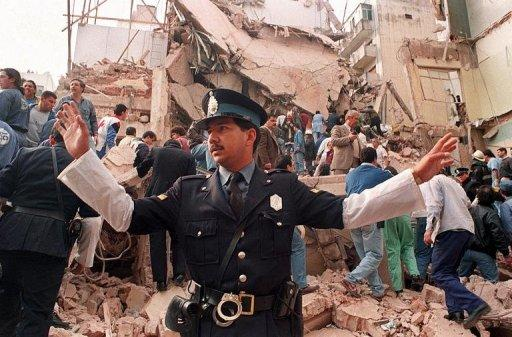 A policeman prevents people from approaching the site of a explosion that destroyed a Jewish aid society in 1994
