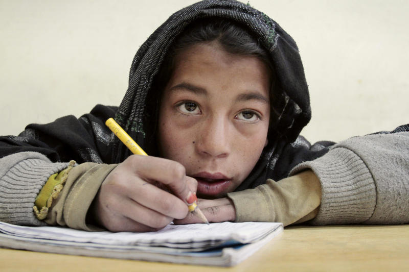In this Thursday, Feb. 21, 2013 photo, Fatema, 10, takes notes during a math class at the Afghanistan's Children - A New Approach (ASCHIANA) center in Kabul, Afghanistan.  The impending withdrawal of U.S. and other foreign combat forces from Afghanistan means more than a loss of firepower. International aid is also on the decline because of donor fatigue and fears of deteriorating security after nearly 12 years of war. Worried about losing hard-won gains, aid organizations are racing to finish projects or find new sources of funding to provide basic services that the weak central government has been unable to deliver. (AP Photo/Musadeq Sadeq)