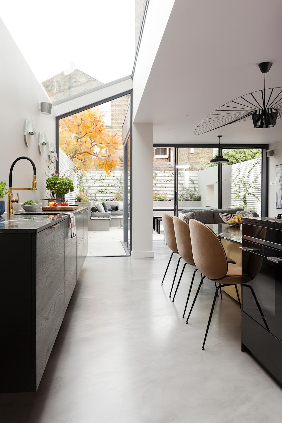 A kitchen with a glazed sloping roof and sliding doors leading to the garden