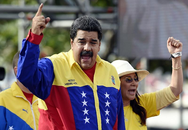 Venezuelan president Nicolas Maduro (L) and first lady Cilia Flores (R)  greet supporters during the closing rally of the campaign on December 3, 2015 in Caracas