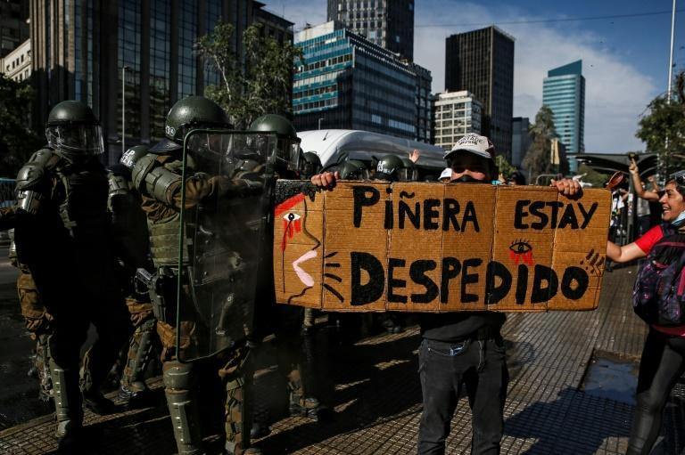 A demonstrator holds a sign reading 'Pinera you're fired' next to riot police during a protest againt President Sebastian Pinera in Santiago, Chile, on November 18, 2020