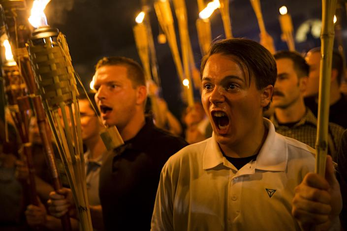 Peter Cvjetanovic, right, along with neo Nazis, alt-rights and white supremacists, encircle and chant at counterprotesters at the base of a statue of Thomas Jefferson after the group marched through the University of Virginia campus with torches in Charlottesville, Va., on Aug. 11, 2017. (Photo: Samuel Corum/Anadolu Agency/Getty Images)