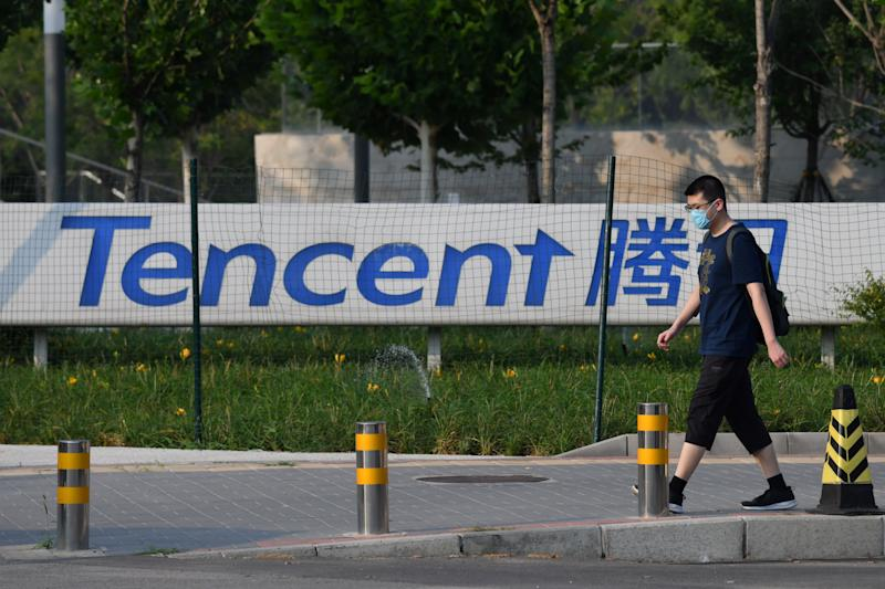 """A man walks past a sign for Tencent, the parent company of Chinese social media company WeChat, outside the Tencent headquarters in Beijing on August 7, 2020. - Beijing on August 7 accused the United States of """"suppression"""" after President Donald Trump ordered sweeping restrictions against Chinese social media giants TikTok and WeChat. (Photo by GREG BAKER / AFP) (Photo by GREG BAKER/AFP via Getty Images)"""