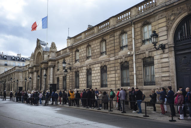People line up to sign a condolence book for late French President Jacques Chirac, Friday Sept. 27, 2019 outside the Elysee Palace in Paris. Mourners are signing memory books, flags are lowered and French politicians from across the spectrum are paying tributes to late President Jacques Chirac. (AP Photo/Kamil Zihnioglu)