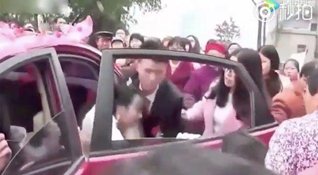 The groom appears to forcibly remove his bride from the car. Source: Weibo/Xingzhi Media