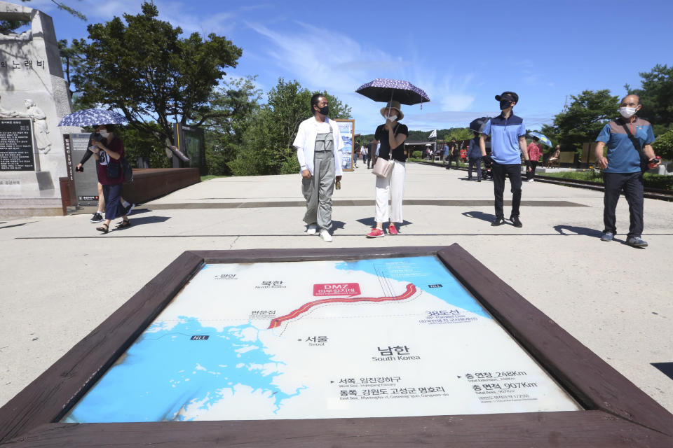 """People wearing face masks to help protect against the spread of the new coronavirus walk by a map of two Koreas showing North Korea's capital Pyongyang and South Korea's capital Seoul at the Imjingak Pavilion in Paju, near the border with North Korea, Sunday, July 26, 2020. North Korean leader Kim Jong Un placed the city of Kaesong near the border with South Korea under total lockdown after a person was found with suspected COVID-19 symptoms, saying he believes """"the vicious virus"""" may have entered the country, state media reported Sunday. (AP Photo/Ahn Young-joon)"""