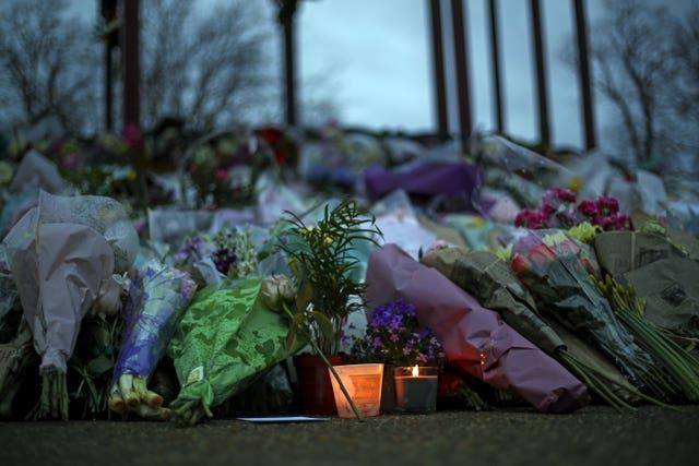 Floral tributes and a candle left at the Bandstand on Clapham Common, London (Steve Parsons/PA)
